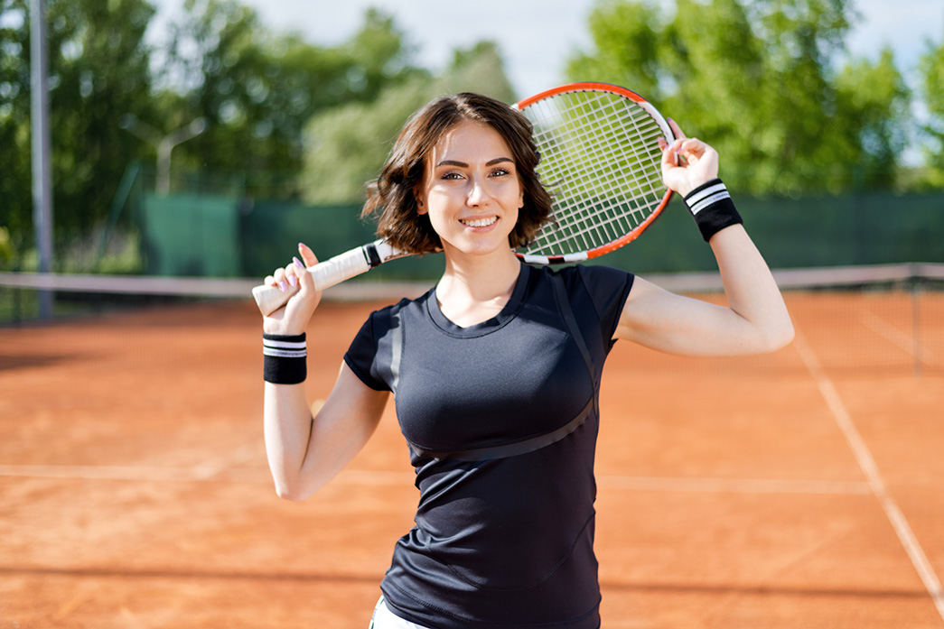 smiling lady at a tennis court